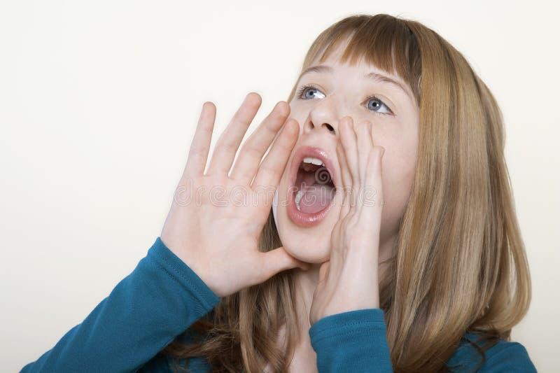 呼喊用手的十几岁的女孩杯在嘴附近 免版税库存照片