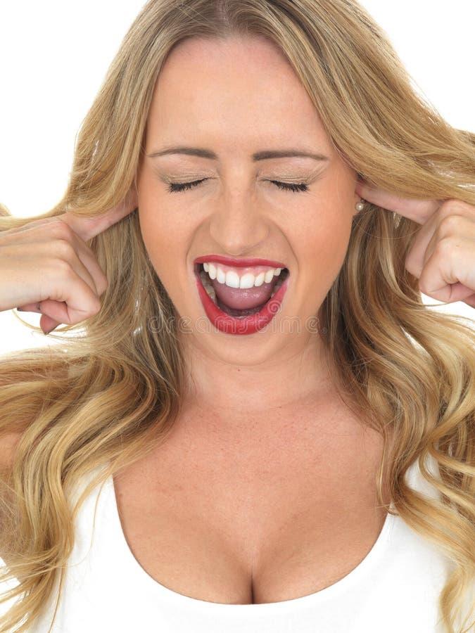 呼喊的少妇不听与在耳朵的手指 免版税库存照片