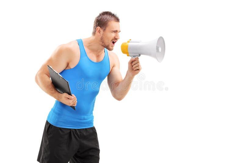 呼喊通过扩音机的男性健身教练 免版税库存照片