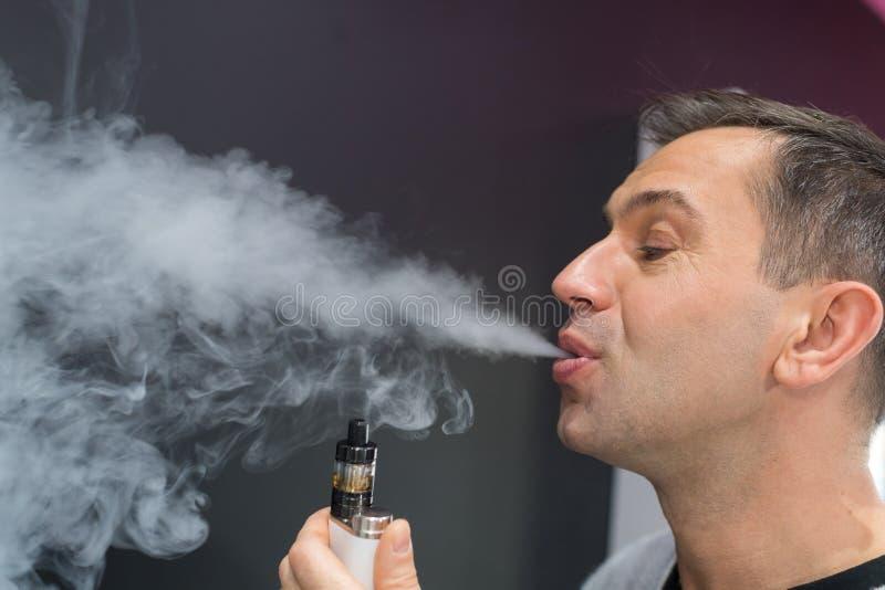 呼气从电子香烟的人蒸气 库存照片