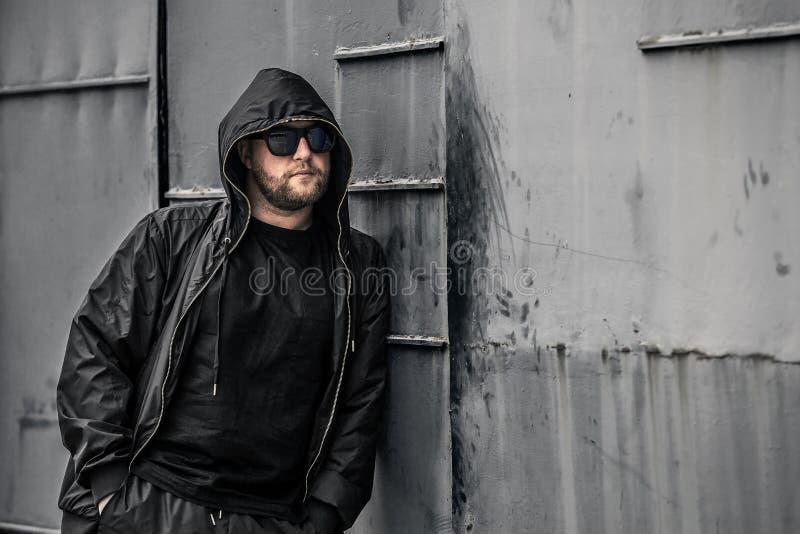 年轻和严肃的交谈者概念性照片在黑色的用拉锁拉上夹克