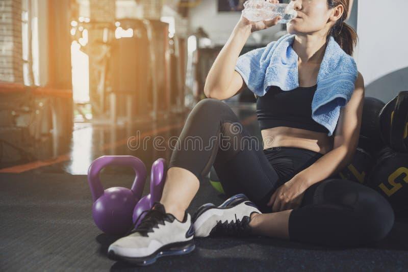 和休息在锻炼或锻炼以后的体育妇女在健身健身房与蛋白质震动或饮用水坐地板 ?? 免版税库存照片