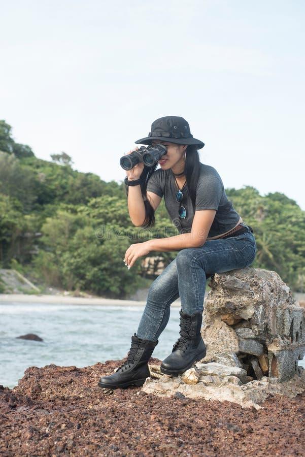 和休息坐岩石和看通过双筒望远镜的亚裔俏丽的女性 库存图片