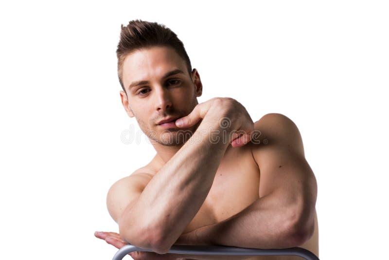 和休息坐椅子的后面的赤裸年轻人 免版税图库摄影