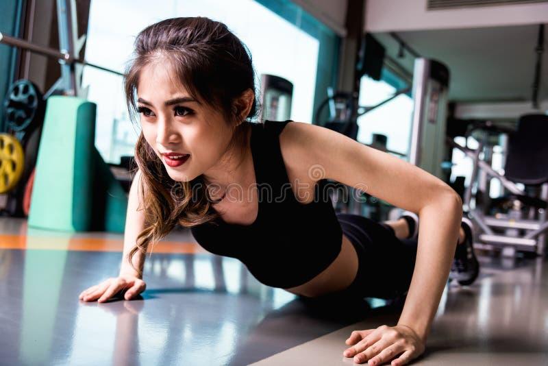 和做在健身健身房的少妇有些俯卧撑 免版税图库摄影
