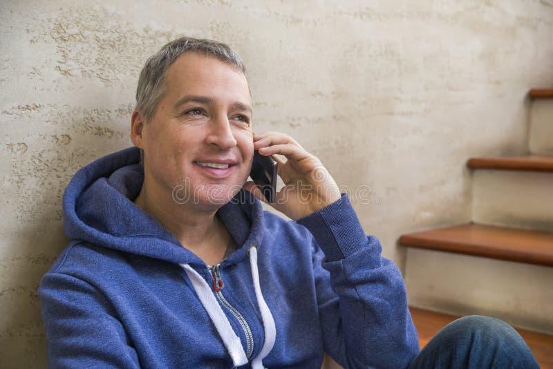 年轻和健康人在家微笑和谈话在巧妙的电话 免版税库存图片