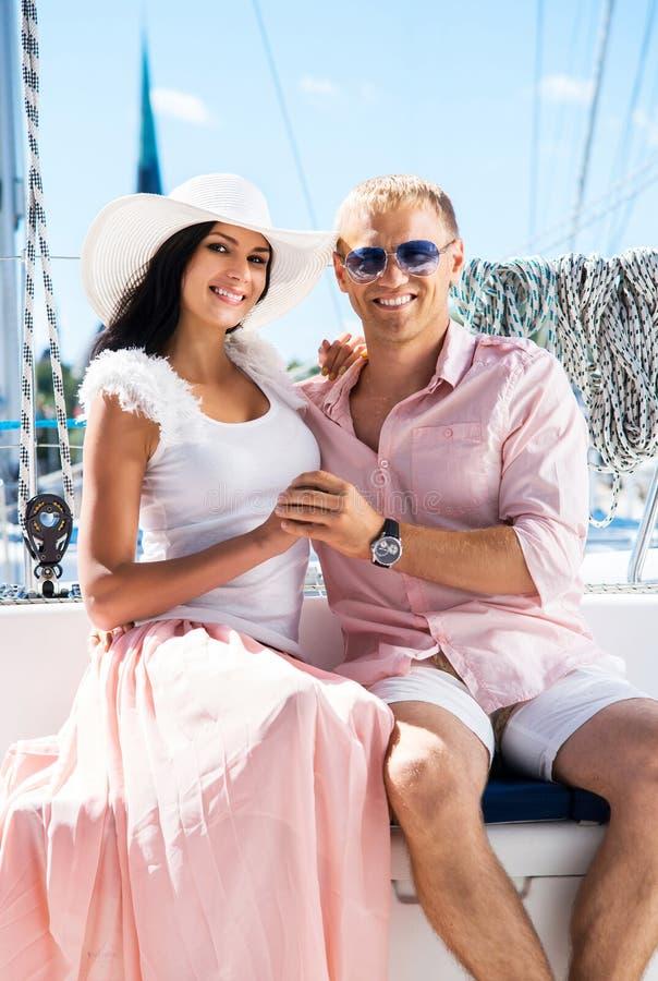 年轻和可爱的夫妇在小船的一个假期 免版税库存图片