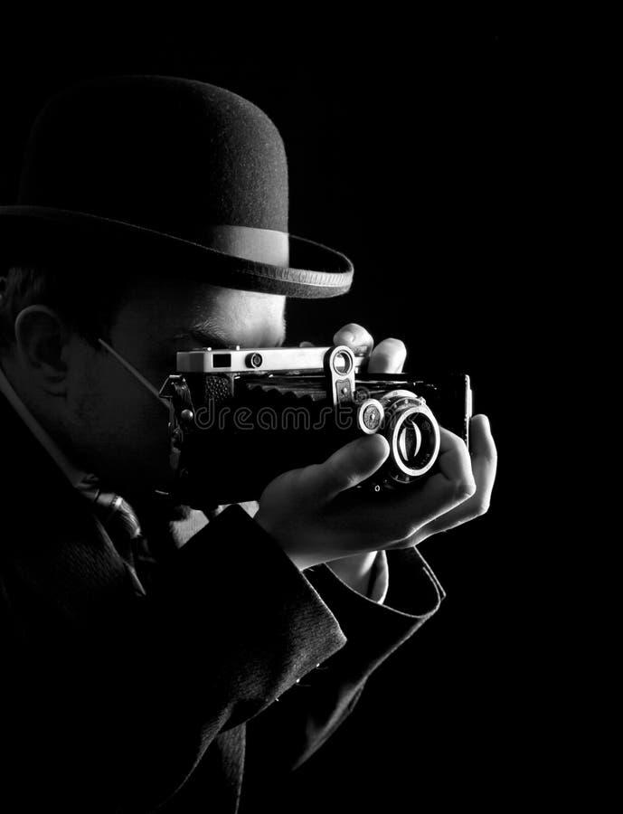 年轻和可爱的摄影师葡萄酒衣服的和有减速火箭的照片照相机的 免版税库存图片