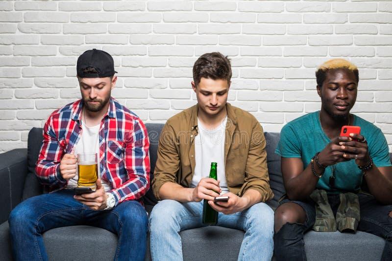 和吃比萨的可爱的年轻混合的族种人在家停留,饮用的啤酒,当使用他们的智能手机全部在同样时 库存图片