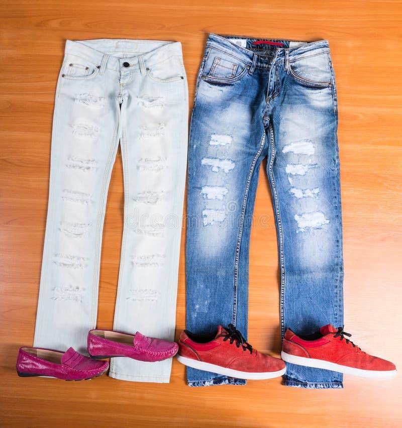 他和她的蓝色牛仔裤放置与鞋子 库存照片