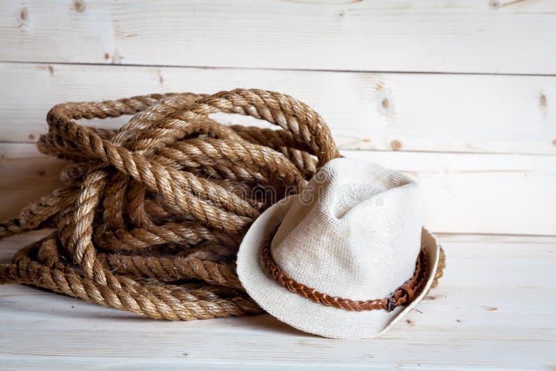 绳索和妇女在牛仔样式的` s草帽在木背景 库存照片