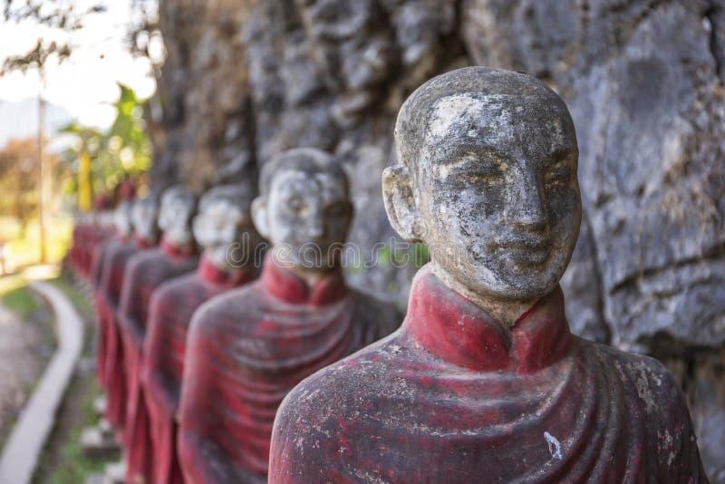 和尚向雕象扔石头荡桨在Kaw钾Thaung洞, Hpa-an,缅甸 免版税库存图片