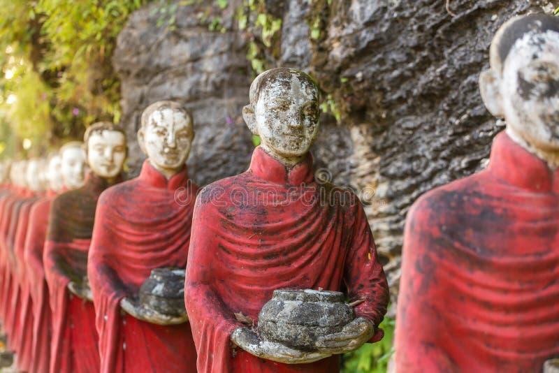 和尚向雕象扔石头荡桨在Kaw钾Thaung洞 库存照片