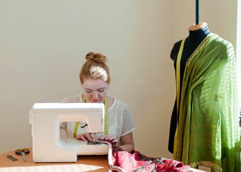 和工作在演播室的裁缝坐在缝纫机,时装模特 免版税库存照片