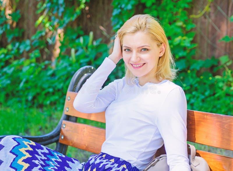 和平和宁静 您为什么需要断裂 放松在公园的妇女白肤金发的作为断裂 女孩坐放松的长凳  免版税库存图片