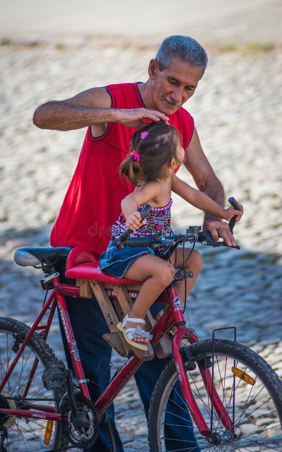 和平和爱以一个女孩和盛大父亲加勒比五颜六色的殖民地城市,哈瓦那,共产主义古巴,美国街道的  免版税图库摄影