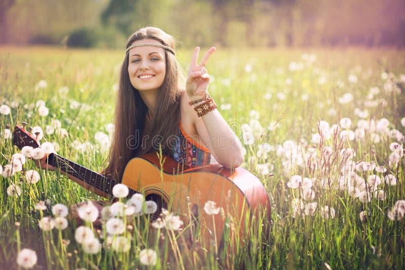 给和平标志的微笑的嬉皮妇女 免版税库存图片