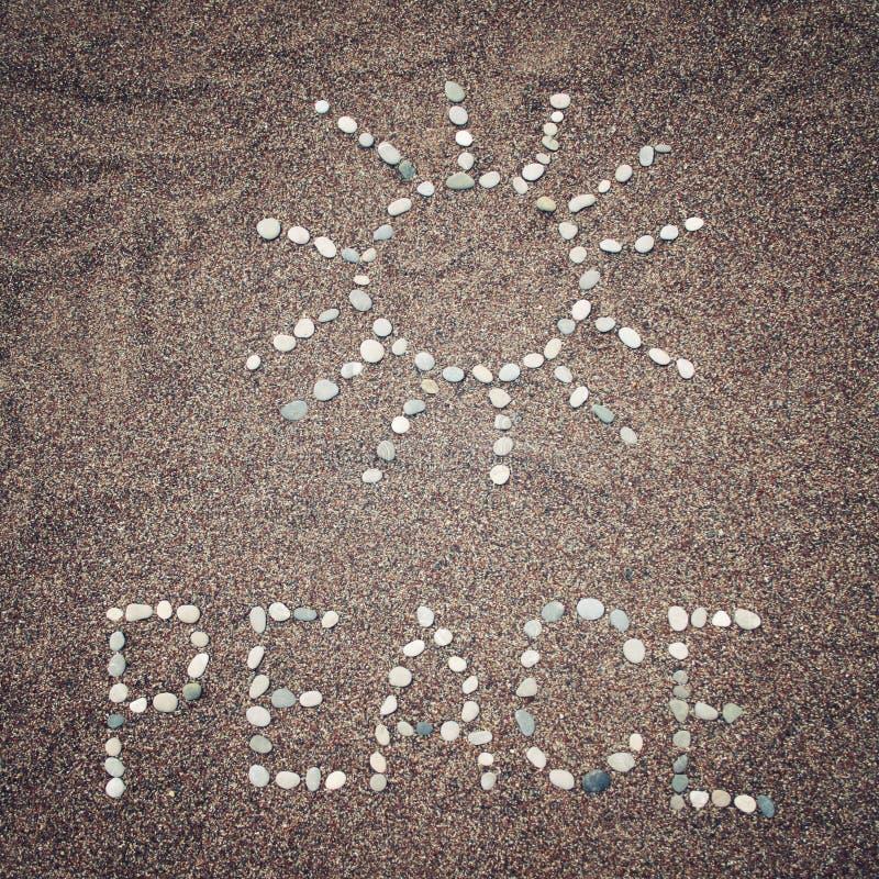 和平词和太阳标志在沙子-被定调子的照片 图库摄影