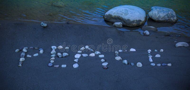 `和平`词写与小卵石在沙子 免版税库存照片