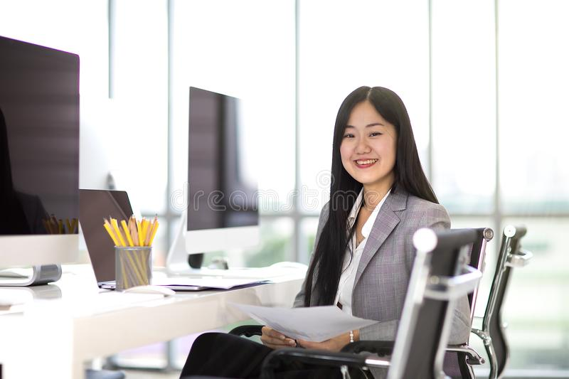 和微笑坐在m的椅子的美丽的亚裔女商人 免版税库存图片