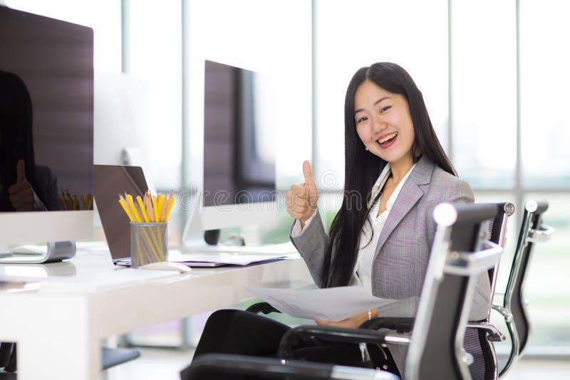 和微笑坐在m的椅子的美丽的亚裔女商人 免版税库存照片