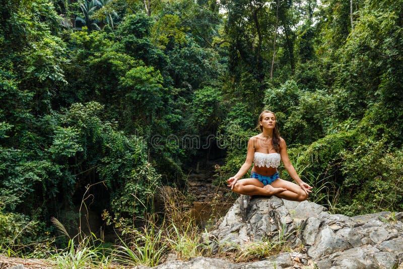 和思考在森林里的女孩坐岩石 库存照片