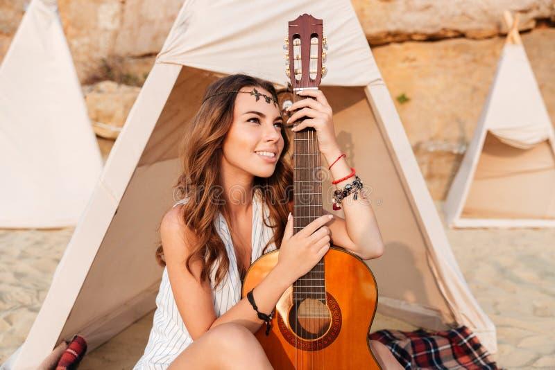 和拿着在圆锥形小屋的愉快的妇女吉他坐海滩 免版税库存图片