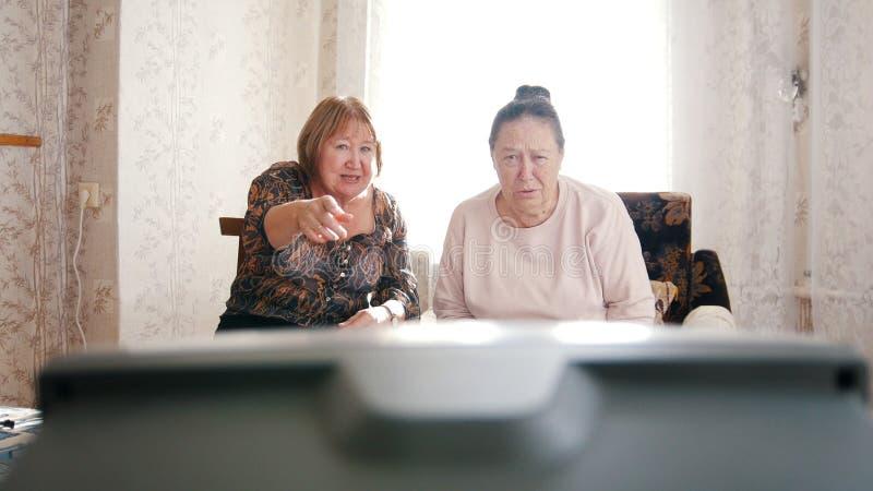 和指向屏幕的年长妇女坐扶手椅子,手表电视 库存图片