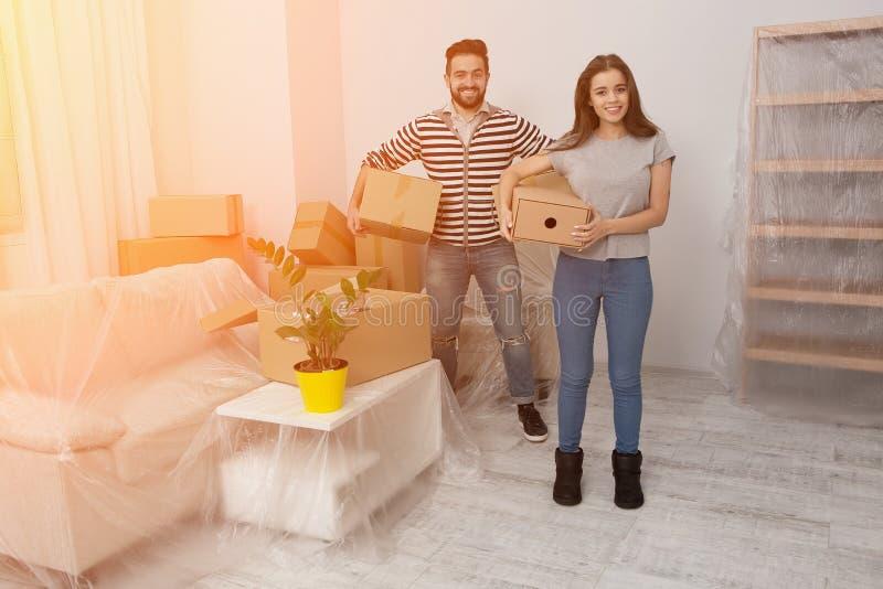 和搬入一个新的家的愉快的年轻夫妇打开或包装盒 免版税库存图片