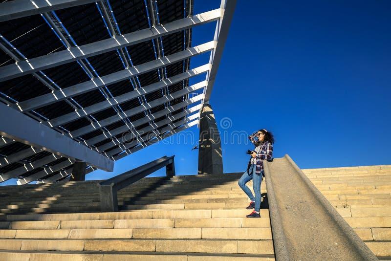 年轻和时髦的妇女在台阶站立在口岸论坛,巴塞罗那,西班牙的巨大的太阳电池板旁边 免版税库存图片