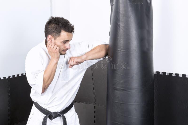 和服投掷的拳打的年轻人在一个重的沙袋 库存照片