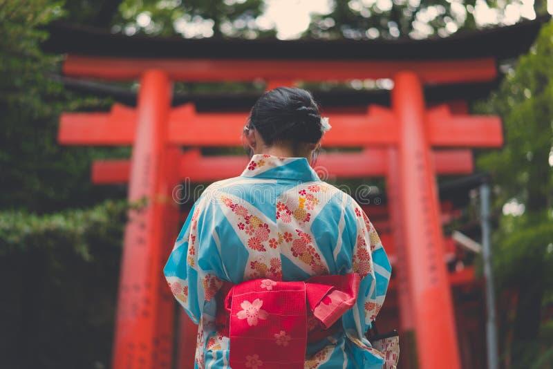 和服的日本妇女在鸟居隧道前面 免版税库存图片