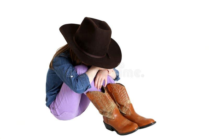 和生气与她的头的女牛仔下来坐她的膝盖 库存图片
