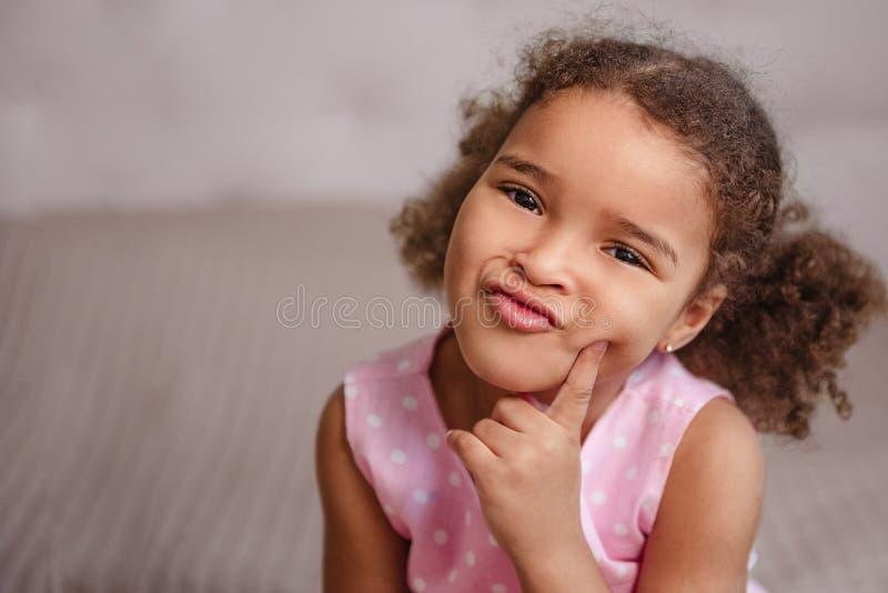 和看想出在中立backgroun的乐趣做鬼脸的女孩 库存照片
