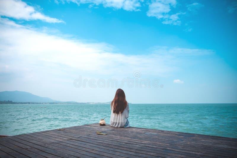 和看海和蓝天的白色礼服的一名美丽的亚裔妇女坐木阳台 库存图片