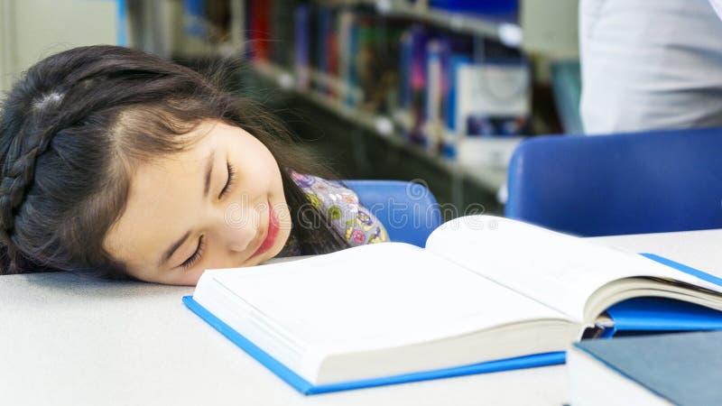 和睡觉与书的兴高采烈的亚裔逗人喜爱的女孩坐选项 图库摄影