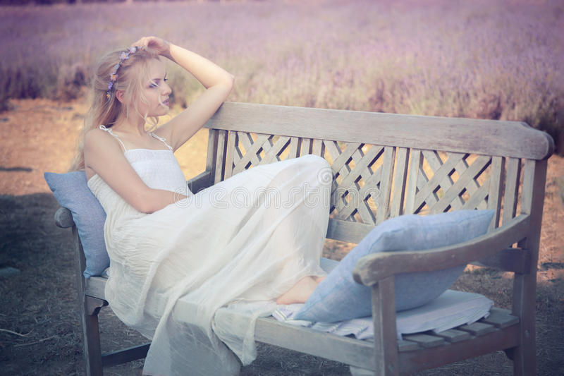 年轻和美丽的妇女坐长凳 免版税图库摄影