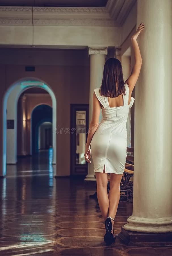 年轻和美丽的妇女(女孩)白色礼服在宫殿,站立近在巴落克式样的柱子 免版税图库摄影