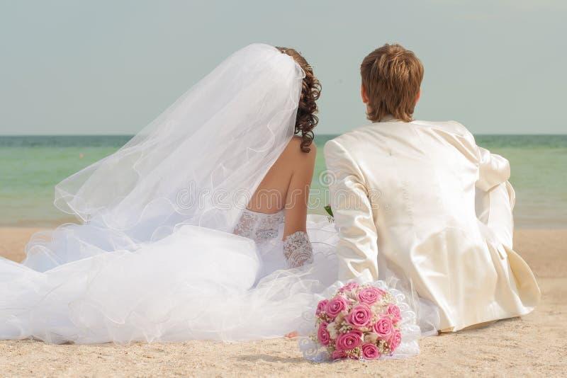 年轻和美丽的新娘和新郎在海滩 免版税图库摄影