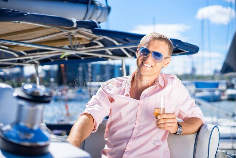 年轻和英俊的人用在小船的香槟 库存照片