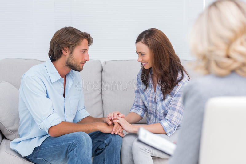 和解在长沙发的夫妇 免版税库存照片