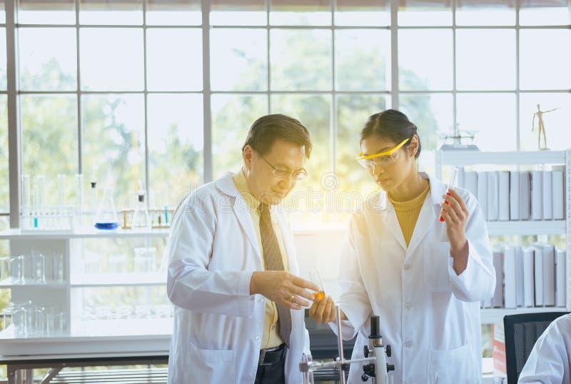 和解释研究信息的亚裔科学家在实验室里 图库摄影