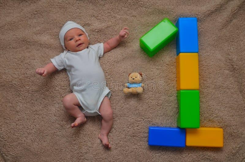 和计数概念的逗人喜爱的新出生的男婴说谎与玩具-生日,庆祝 免版税图库摄影