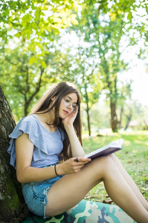 和读她喜爱的书的年轻女人坐o绿色gras在树下在一个好晴朗的夏天 库存照片