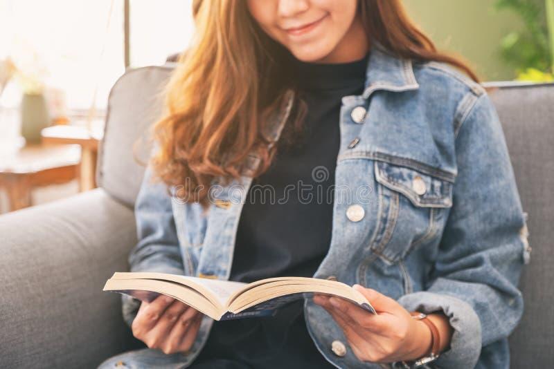和读葡萄酒新颖的书的一名美丽的亚裔妇女坐沙发 免版税库存照片