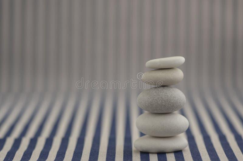和谐和平衡,小卵石岩石石标,在白色和蓝色镶边背景,岩石禅宗雕塑,一个塔的简单的世故石头 免版税库存图片