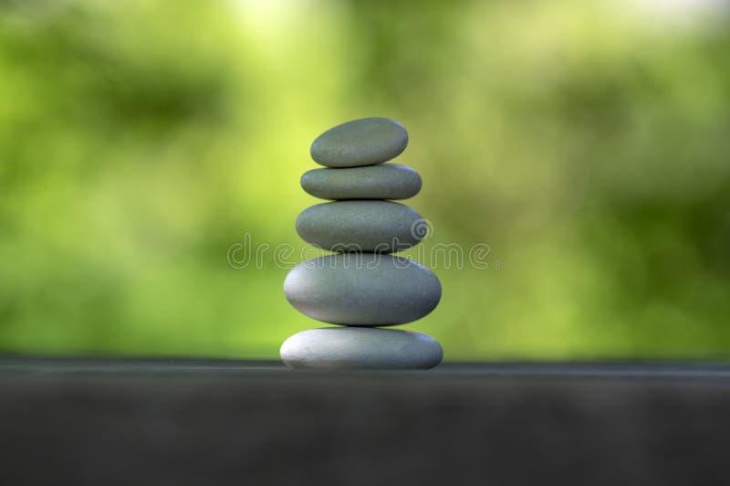 和谐和平衡,石标,在木桌,自然绿色背景,朴素岩石禅宗雕塑上的简单的世故小卵石 库存照片