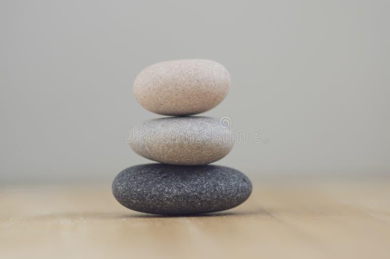 和谐和平衡,石标,在木轻的白色灰色背景,朴素岩石禅宗雕塑的简单的世故小卵石 免版税库存照片