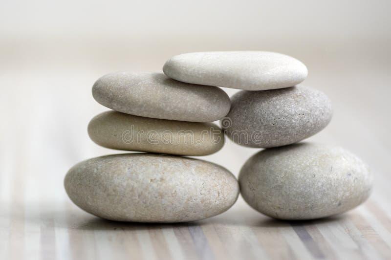 和谐和平衡,石标,在木轻的白色灰色背景,朴素岩石禅宗雕塑的简单的世故石头 图库摄影