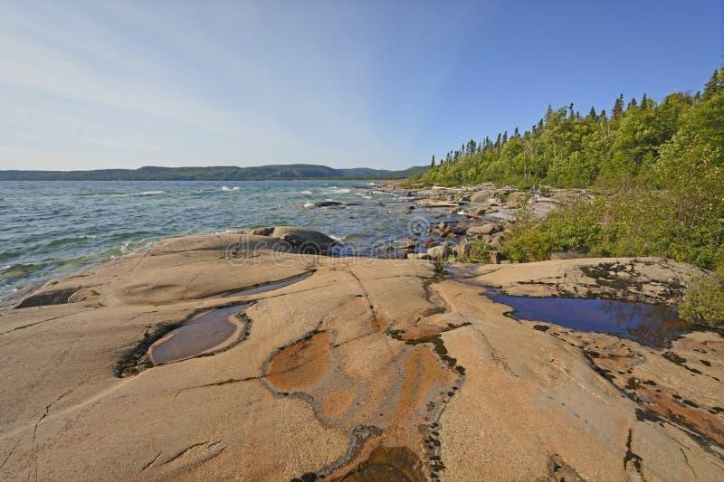 水和破旧的岩石在偏僻的海岸 库存图片